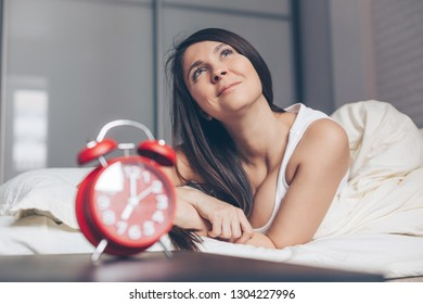 Rest, inspiration, creativity, comfort and people concept. Happy young woman dreaming in bed at home bedroom. Red alarm clock in foreground