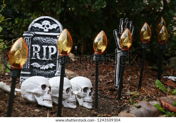 Rest in Peace RIP Gravestone Halloween Decoration with Skulls Below and Golden Lights in the Foreground in the Lawn Next to Bushes in Burke, Virginia on Halloween