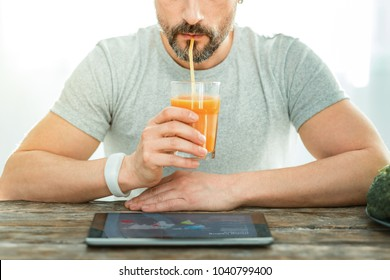 Rest with pleasure. Concentrated pleasant relaxed man sitting by the table looking at the laptop drinking juice.
