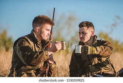 Rest for real men concept. Hunters with rifles relaxing in nature environment. Hunting with friends hobby leisure. Hunters friends enjoy leisure. Hunters satisfied with catch drink warming beverage.