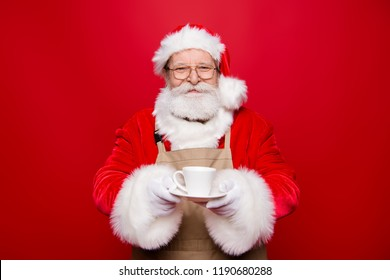 Rest relax concept. Careless carefree kind cheerful positive glad calm aged Santa white beard costume offers to client drink cup of hot aroma tea or coffee isolated on vivid red background