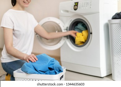 Rest, relax and enjoying of laundry process. Attractive and cheerful woman takes out the clothes from white washing machine inside flat with bright interior