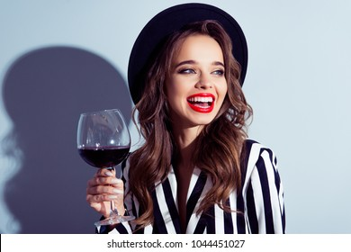 Rest relax lifestyle concept. Close up portrait of delightful laughing excited win winner posh fashionable fancy woman tasting old expensive wine from big glass in hand isolated on gray background