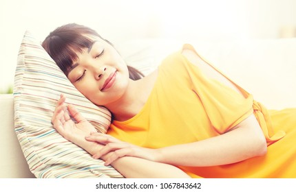 rest, relax and people concept - happy asian teenage girl or young woman sleeping on sofa at home