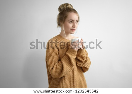 a5e6d1379c Beautiful young female wearing oversize pullover keeping eyes closed and  holding