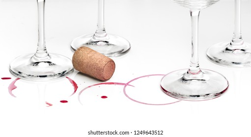 Rest of wine empty glasses and cork against white background. Wine or alcohol consume concept.