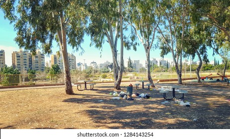 Rest zone with concrete tables and some swings for children in the eucalyptus grove opposite residential buildings. There are traces of picnic in form of throwing litter around the garbage bin.
