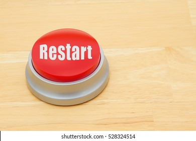 A Restart red push button, A red and silver push button on a wooden desk with text  Restart