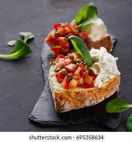 Restaurant appetizer on black background. Crusty bruschetta with concasse tomatoes, stracciatella cheese decorated with spinach. Delicious and healthy meals, copy space, closeup