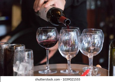 Restaurant bartender server pour bottle of wine into glass for customer drink order during fine italian dinner meal. Red wine made from grapes