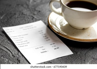 restaurant bill, card and coffee on dark table background