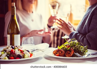 Restaurant or cafe table with plate of salads and wine. Two people talking on background. Toned picture