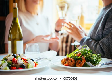Restaurant or cafe table with plate of salads and wine. Two people talking on background