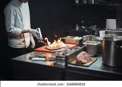 Restaurant Chef cook preparing salmon filet flambe.