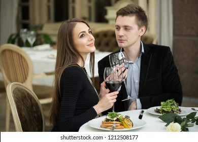 restaurant, couple and holiday concept - smiling couple drinking red wine