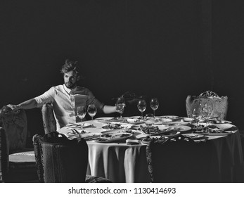 Restaurant critic. Handsome young man with beard and blond hair drinks wine from glass sitting at table with leftovers or residues food on dirty plates after banquet dinner in restaurant on dark