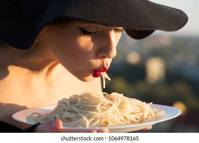 restaurant critic tatse italian pasta. restaurant, woman with red lips in black hat eating pasta.
