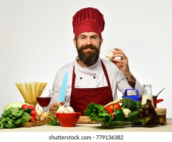 Restaurant cuisine concept. Chef prepares meal. Cook with smile in burgundy uniform sits by kitchen table with vegetables and kitchenware. Man with beard holds mushroom and knife on white background