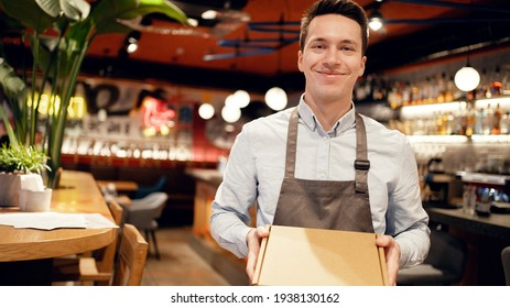 a restaurant employee receives a delivery from a courier. Sending pizza lunch in a package to your home. Work in a small restaurant in the city center. Smiles favorite work