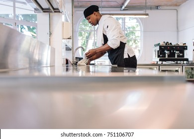 Restaurant employee soaking a cloth in water for cleaning counter. Man working at commercial kitchen.