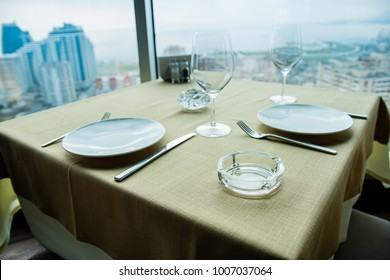 Restaurant empty table for two with large window view.