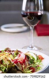Restaurant food concept - salad and glass of red wine