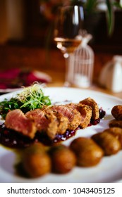 Restaurant food with fresh ingredients - pork tenderloin with grenaille potatoes and fresh salad in luxury restaurant environment, cutlery and glass of wine