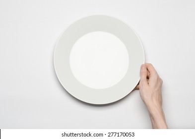 Restaurant and Food theme: the human hand show gesture on an empty white plate on a white background in studio isolated top view