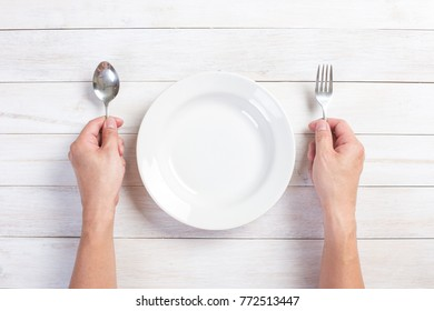 Restaurant and Food theme: human hand holding a fork and spoon