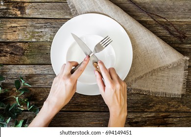 Restaurant and food theme: human hands show on a wooden background. Healthy food theme: hands holding knife and fork on a plate, top view