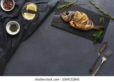Restaurant food - whole grilled dorado with lemon slices on black restaurant table, top view, copy space