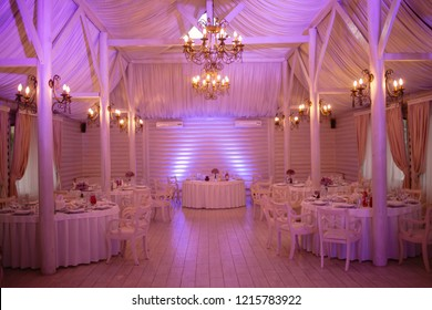 restaurant hall, wedding ceremony. The restaurant hall is decorated for the wedding ceremony. Restaurant / bar lighting in purple and pink colors