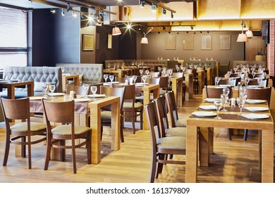 Restaurant hall with wooden furniture and walls of red bricks