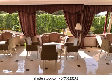 An restaurant interior with garden view from the window.