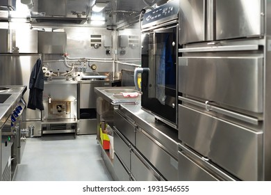 Restaurant kitchen with chrome equipment. Kitchen of working restaurant without people. Equipment for fast food restaurant. Equipment for confectionery shop. Professional kitchen furnishing for cafe
