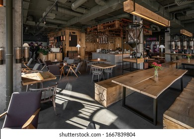 Restaurant in a loft style with textured wooden walls and concrete columns. There are tables with chairs, many shelves with bottles, glass coffee bean dispensers, coffee machines and equipment.