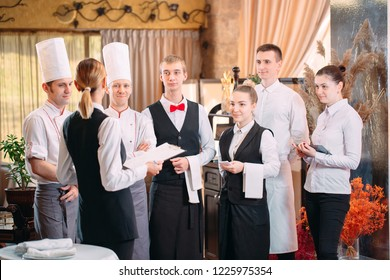 restaurant manager and his staff in kitchen. interacting to head chef in commercial kitchen