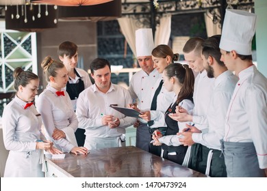 Restaurant manager and his staff in terrace. interacting to head chef in restaurant