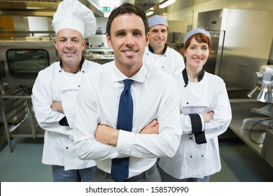 Restaurant manager posing in front of team of chefs smiling at camera