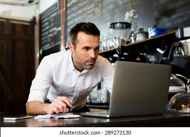 Restaurant manager working on laptop, counting profit