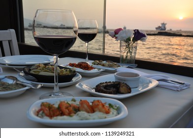 A restaurant on the sea side. It's a romantic dinner. Red wine, fish and appetizers. It's a great atmosphere. Marriage proposal or dinner for Valentine's Day.