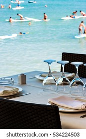 Restaurant on the seashore with the table set. Vertical image.