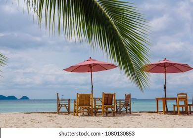Restaurant on the tropical beach with pink umbrellas, tables an chairs