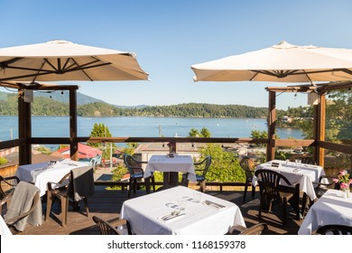 A restaurant patio with tables set overlooking Gibsons, BC, on a bright sunny day