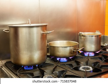 Restaurant pro kitchen with stainless steel pans in fire