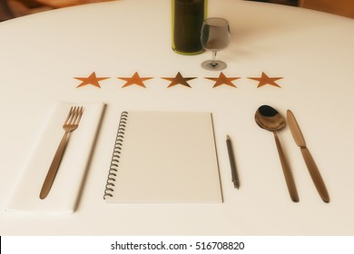 Restaurant rating concept. Close up of dining table with wine, cutlery, spiral notepad and five stars. 3D Rendering