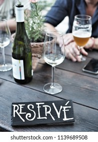 Restaurant reserved table sign. Bottle and glass of white wine, glass of bear on wooden table.