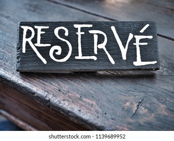 Restaurant reserved table sign on wooden table.