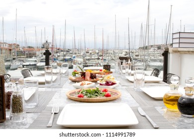 Restaurant at sea shore against blue water and Yacht Port of Aegean sea on Cesme. Marble Table with plate of beef appetizers, cheese, bread, Carpaccio, raki, ouzo and wine. Copy space for text area.