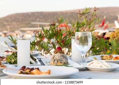 Restaurant at sea shore against blue water and Yacht Port of Aegean coast on Cesme. Luxury table with plate of fish appetizers, cheese, meze, salad, octopus, raki and ouzo. Copy space for text area.